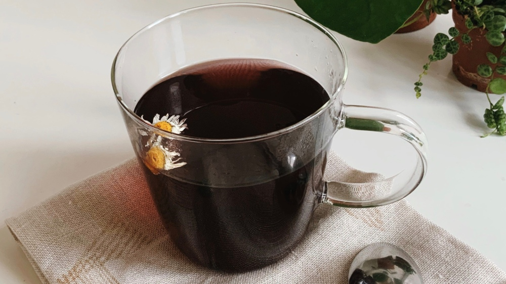 A clear mug with dark coloured liquid inside - elderberry and hot water